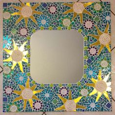 """""""Beaches""""...This is an all hand cut, handmade mosaic mirror. It is 24"""" X 24""""  """"flowers/Suns """", in various shades of blue and green, with yellow accents, with a hint of purple  It is grouted in cwhite."""