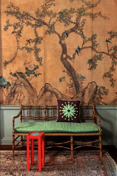 silk chinoiserie in copper hues set off by a red stool