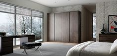 Burnt oak handleless design wardrobes. A gorgeous grey bedroom with modern handlelss style wardrobes and drawers in a rustic look dark oak finish. Fitted bedroom furniture by Just Click Kitchens.