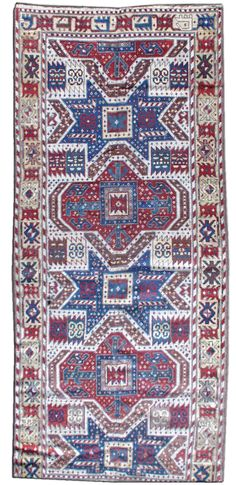 """A late 19th century Caucasian Kazak antique rug, the ivory field with a multitude of minor stellar motifs around a central column of linked alternating indigo stellar and rust-red stepped medallions, with square central panels containing arabesque motifs, within a light yellow serrated geometric border. Circa: 1880, Size:  9' × 4'6""""."""