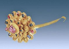 A gold hairpin in the shape of a chrysanthemum (flowering plant). It has a large ruby at center and a mix of smaller sapphires and rubies on its petals. The diameter at the largest point is 11.7 centimeters (4.6 inches). The total weight of the artifact is 218.2 grams (more than 7.5 ounces), found inside the Ming Dynasty tomb of a woman named Lady Mei (1430 1474).