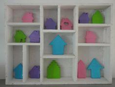 Huisjes gemaakt van klei geverfd in pasteltinten. Sfeervol bij elkaar in een letterbak.