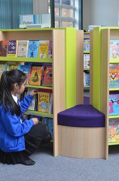Girl browsing school library bookshelves