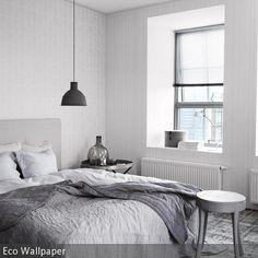 Dieses moderne Schlafzimmer in Grau-Weiß zeichnet sich durch elegante Schlichtheit aus. Ein großes Bett, ein Hocker – keine Schnörkel. Textilien sorgen für Gemütlichkeit. Eyecatcher: die Mute-Leuchte über dem Bett.