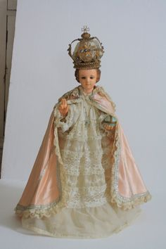 Antique Infant Jesus of Prague Statue Broken Hand Glass Eyes Infant with Peach Vestments Crown Necklace. $685.00, via Etsy.