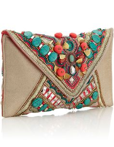 Get into the ethnic trend that has been swooping the runways with this bright and fun embellished envelope clutch with large turquoise beading, pink pom poms and bright beading and gems.