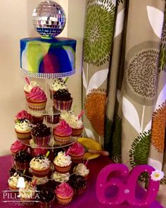 60th birthday cake and cupcake tower, topped with a glitter ball