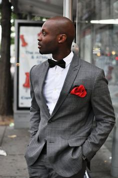 Not a big fan of bowties, but he plays it off very well. The subtle use of red adds a great touch to the monochromatic tone.