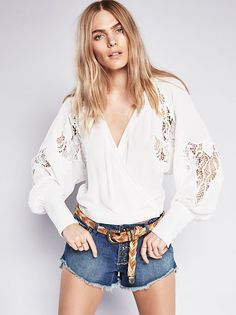 Cropped to the natural waist this long sleeve blouse is pieced with allover beautiful crochet detailing. With hidden button closures on the waist band this wrap style top has a plunging surplice neckline.