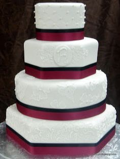 Four tier round and hexagon custom wedding cake with elegant brushed royal icing flowers, curlicues, monogram,edible pearls, garnet and blac...