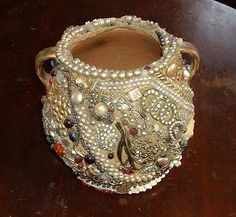 This is a crafted piece.  Makes you want to buy a bunch of vintage costume jewelry and make one of your own.      OLD Crow Antiques and Amish Tours: Vintage Crockery/Crock Memory Pot or Jug    http://oldcrowantiques.blogspot.com/2010/01/vintage-crockerycrock-memory-pot-or-jug.html#