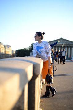 Look super colorido para semana de moda em Paris, street style, com saia laranja de couro Patricia Viera, moletom estampado, botas e bolsa preta tipo saco Alaïa.
