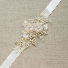 This Ivory/Champagne Floral sash belt is handmade with hand pressed ivory, champagne/nude chiffon flowers, tulle, silver rhinestones, champagne pearls,