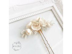 Propletená krása květů. Svěží moderní aranžmá z ručně vyrobenýchkrémových (ivory) květů, zakončené po obou stranách krajkou upletenou z drobných korálků.Elegantní moderní detail, který svou velikostí nezastíní nevěstinu krásu, ale jemně ji doplní. Cestuje v designovém dárkovém balení.