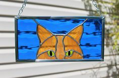 """This mischievous cat has a butterscotch ginger coat with wisps of white. His eyes are bright green with black hand painted pupils. The paint is designed for glass, was baked on and will not wipe off. A bright sapphire blue glass with a gentle wavy texture forms the background of the panel. The panel measures 4 1/4"""" tall, 8 1/4"""" wide. The glass in this piece was carefully cut, wrapped in copper foil and soldered. The solder lines are silver in color. It is framed with zinc came. A ..."""