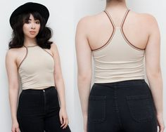 Cream colored crop top in a medium weight polyester spandex blend. Has a racerback and the straps are a striped retro look elastic. Has a 70s feel,