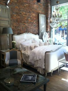 Love the white elegant bedding. Like speeding on a cloud. The red brick is beautiful too! Adds a rustic touch to the room.