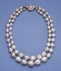AN IMPORTANT ANTIQUE TWO STRAND PEARL NECKLACE Comprising twenty-eight and twenty-nine graduated pearls, total weight, excluding clasp, approximately 1,852 grains (463 carats), measuring 6.8 to 15.5 mm. with seed pearl spacers and diamond foliate terminals to the vari-cut diamond cluster clasp, pearls 18th century or earlier, clasp later, 40.5 cm. long