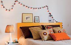 Para não ter de investir em marcenaria planejada no quarto, destaque outros detalhes da decoração. Aqui, o truque foi turbinar a cama com almofadas coloridas. O pisca-pisca acima da cabeceira também chama a atenção.