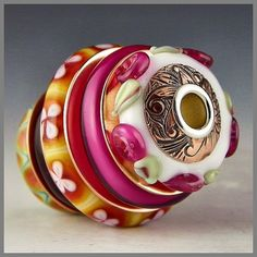 My latest stacker bead: On this one Ive stacked five disk beads with shiny copper spacers, floral patterned copper beadcaps, and a sterling silver core to create a one-of-a-kind pendant bead that is sure to be an eye-catcher! These beads were done in opal yellow, bright fuchsia (gold pink aka Rubino Oro), copper green, and white - with a bit of sparkling dichroic added into one of the discs for some pink glitter!    I finished this bead with a sterling silver core and copper beadcaps, and…