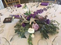 Wild n' wonderful centerpiece of guinea feathers, purple larkspur, seeded eucalyptus, blue bird roses Seeded Eucalyptus, Centerpieces, Table Decorations, Blue Bird, Wedding Events, Feathers, Floral Design, Roses, Purple