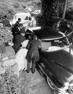 Elevated view as well-wishers gather around the car that carried newly wed future US President John F Kennedy and Jacqueline Kennedy to their wedding reception, Newport, Rhode Island, September