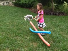 Horse jumps out of pool noodles and wooden dowels.