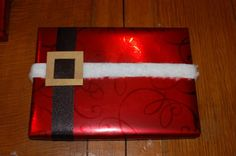 wrapped in red paper with black ribbon, furry ribbon and a gold(paper) buckle