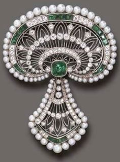 A Belle Epoque emerald, diamond, and seed pearl pendant/brooch, by J.E. Caldwell & Co. The pierced old European-cut diamond plaque, enhanced by alternating old European-cut diamond and calibré-cut emerald detail, to the seed pearl trim and central sugarloaf cabochon emerald, suspending a pendant of similar design, mounted in platinum, circa 1915, in a green leather case Signed J.E.C & Co., no. 31682 (indistinct). Christie's.