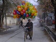 A vendor pushes his balloon-laden bike through Kabul