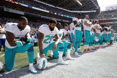 NFL players' national anthem protests   -  From left, Miami Dolphins linebacker Jelani Jenkins, running back Arian Foster, safety Michael Thomas, and wide receiver Kenny Stills kneel during the singing of the national anthem before a game against the Seattle Seahawks, Sunday, Sept. 11, 2016.
