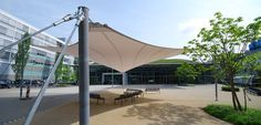 A three-dimensional membrane serves as a shade sail and weather protection roofing.