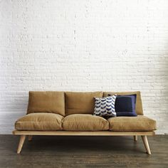 This is a neutral beige coloured Swede sofa that has two blue patterned cushions on top. I love how the curvy seating balances the straight, horizontal, wooden chair stand. The blues act as an accent colour and the patterns adds movement to the sofa.