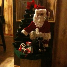 Plastic canvas santa and tree sits on top of 4/4