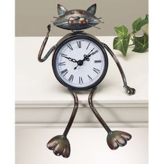 "Bobblehead sitting cat clock is a novelty timepiece. Easy-to-read Roman numerals. Quartz movement; requires one AA battery. Details: - Bronzetone metal. - 5"" sitting height. This product has a Lead Ti"