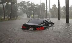 A car is seen in a flooded street in Miami.