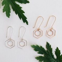These modern earrings feature two wire hexagons dangling from long hooks. Earring length: 1 1/2 inches Available in sterling silver or 14k gold filled.