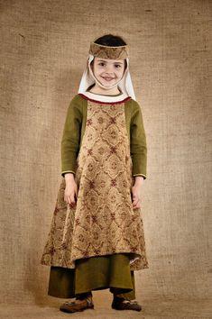 Costume médiéval de noble Dame inspiré de la fin du 13ème siècle composé de 3 pièces : une robe de dessous en lin lavé de couleur verte avec laçage dans le dos, une sur-robe en velours lisse et soyeux et une coiffe assortie réglable, agrémentée d'une sous-gorge et d'un voile en lin écru. Ce modèle est disponible du 4 au 12ans. Tous les costumes proposés par 7 et une Lieues sont de fabrication artisanale et de très grande qualité.
