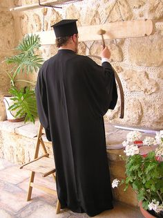 "An Orthodox monk calls to prayer by playing the ""simandro"" in front of the church"