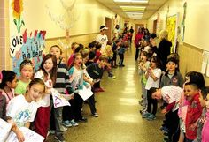 Jen Marra / Ocean City Primary School students wait in the hallway to cheer for the third-graders coming back from their fitness assembly.