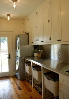 Modern country laundry w/ sorter bins; I like this laundry room with its stainless steel countertop.  I am assuming the washer/dryer is close to the outside wall for venting purposes.  Very gutsy having a wood floor in the laundry room.  AND I love the door!