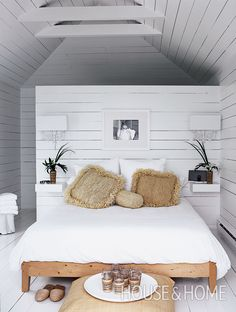 A sea of white creates the perfect casual retreat in this boathouse's narrow upper-level bedroom. | Photographer: Stacey Brandford | Designer: Michelle Lloyd Bermann