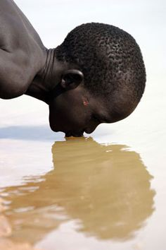 """A Southern Sudanese boy drinks water from the Aquem river, north of Bahr er Gazal"" 