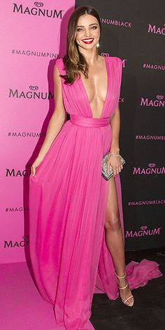 "The Best and Boldest Looks from the Cannes Red Carpet! | MIRANDA KERR | in a hot pink pleated Emanuel Ungaro gown with major cleavage and a super-high slit, plus drop earrings and a sparkly Oroton clutch at the Magnum ""Pink and Black"" party."
