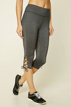 A pair of marled stretch-knit capri leggings with a lace-up hem and a hidden key pocket.