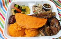 Traditional Chamorro food: red rice, empanada on top, bbq, chicken kelaguin,  finadene (soy sauce), and cucumber