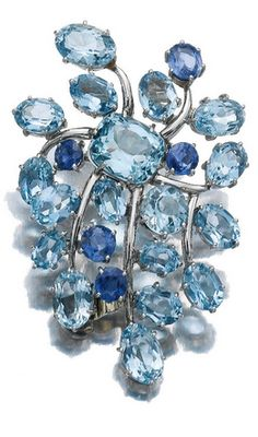 SAPPHIRE AND AQUAMARINE CLIP, SUZANNE BELPERRON, CIRCA 1970 The brooch designed as a spiralling cluster centring on a cushion-shaped aquamarine, surrounded by oval and circular-cut sapphires and aquamarines, French assay and maker's mark for Darde & Fils.