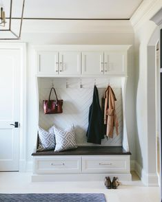 Entryway built in cabinetry with coat hooks and bench seating. Love the herringbone backing detail!