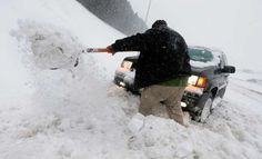 Digging jeep out of snow - Steve Helber/AP