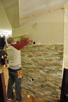 Applying brick/stone to a wall.